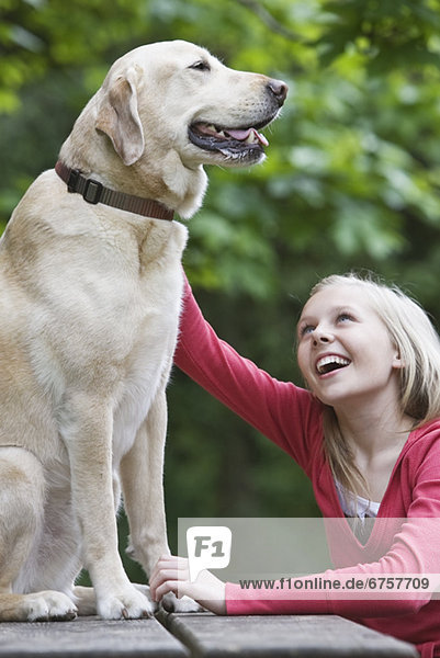 Girl petting dog sitting on picnic table