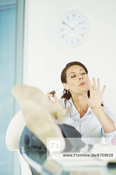 Frau  Schreibtisch  streichen  streicht  streichend  anstreichen  anstreichend  Menschlicher Fingernagel  Menschliche Fingernägel