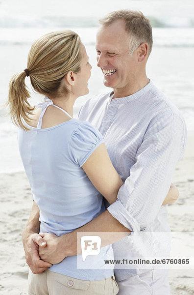 Porträt von paar umarmen am Strand