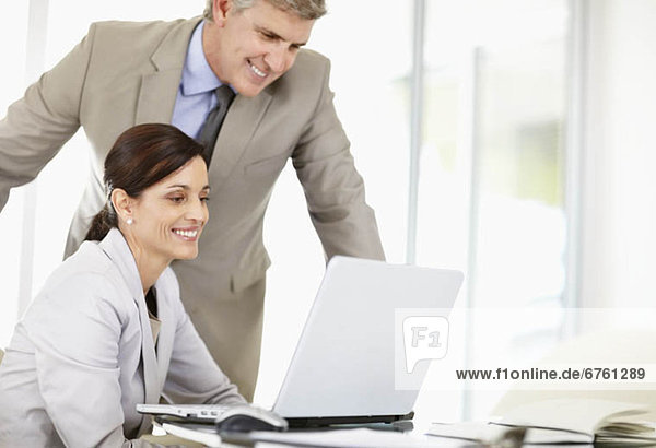 Business associates discussing image displayed on computer screen