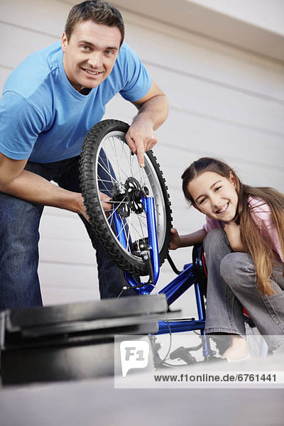 Father with daughter (10-11) fixing bike
