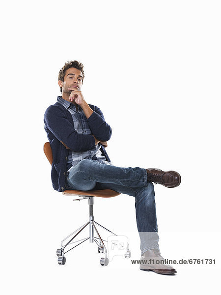 Studio shot of young pensive man sitting on chair