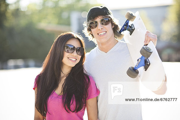 Young multi-racial couple posing with skateboard