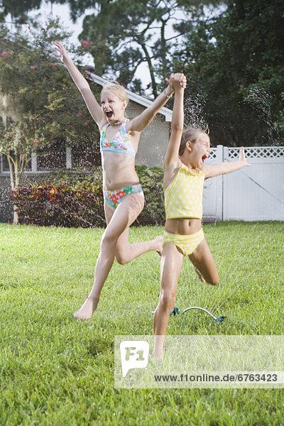 Mädchen durch Sprinkler