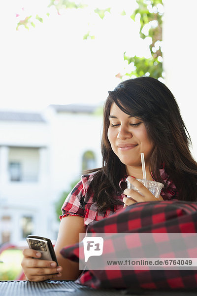 Young woman using phone in outdoor cafe