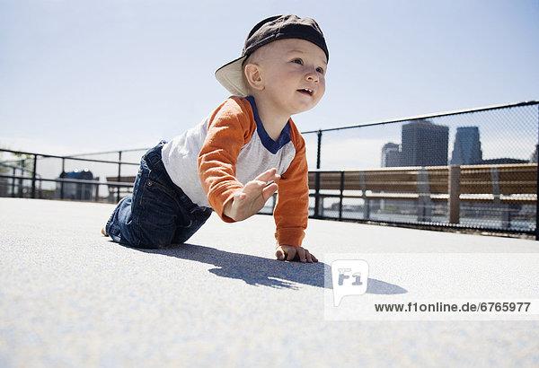 USA  New York City  Brooklyn  baby boy (0-1 years) crawling on sidewalk