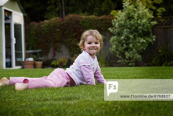 Little Girl Laying in Grass in Backyard  Langley  BC