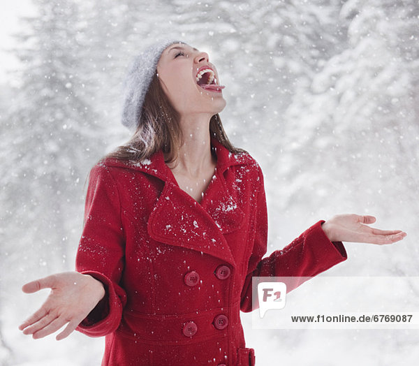 Woman trying to catch snow on her tongue