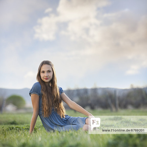 Beautiful long haired woman relaxing on the grass