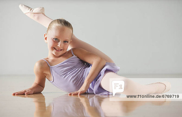 Portrait of female ballet dancer (6-7) stretching in dance studio