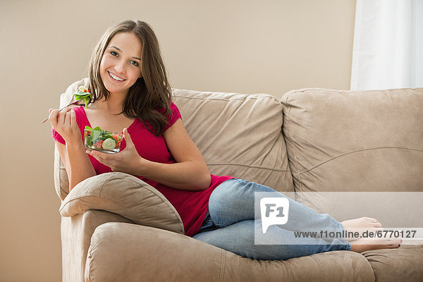 Portrait of young woman eating salad