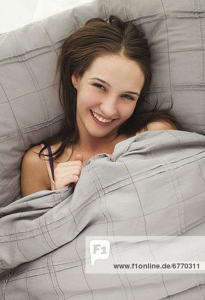 Portrait einer jungen Frau im Bett liegend