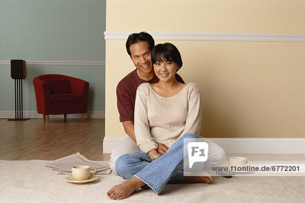 Happy couple sitting together on the floor in their home