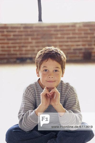 sitzend niedlich süß lieb überqueren Junge - Person jung Schneidersitz Kreuz