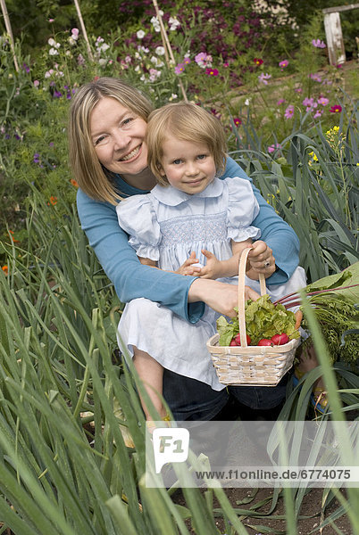 Mother and daughter in an organic garden  Victoria  British Columbia