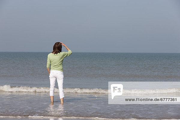 Frau am Strand mit Blick zum Meer