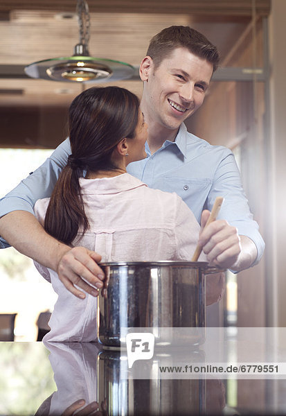 Couple embracing while cooking dinner