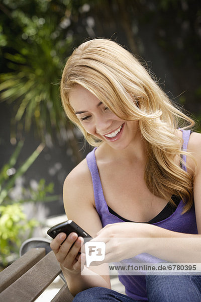 Young woman text-messaging in park