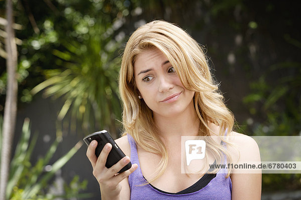 Young woman text-messaging  with facial expression