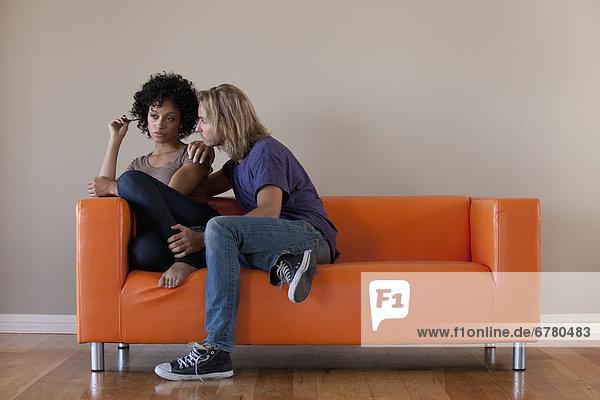 Junges paar auf Sofa sitzend