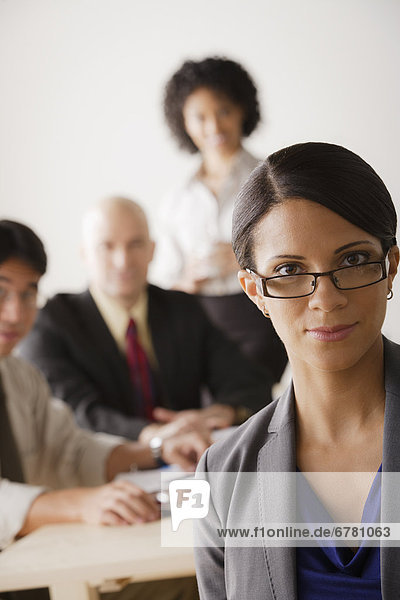 Young businesswoman looking at camera  business team in background