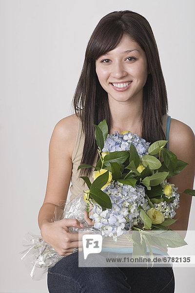 Portrait of junge Frau hält Blumenstrauß
