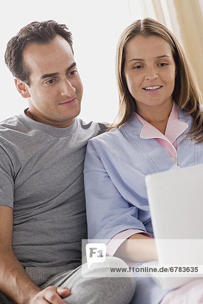 Junges blondes Paar sitzt leicht bekleidet vor einem Laptop - Partnerschaft  fully_released