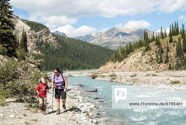 A woman and her son walk along a stream near Bow Lake in Banff National Park,  Alberta,  Canada