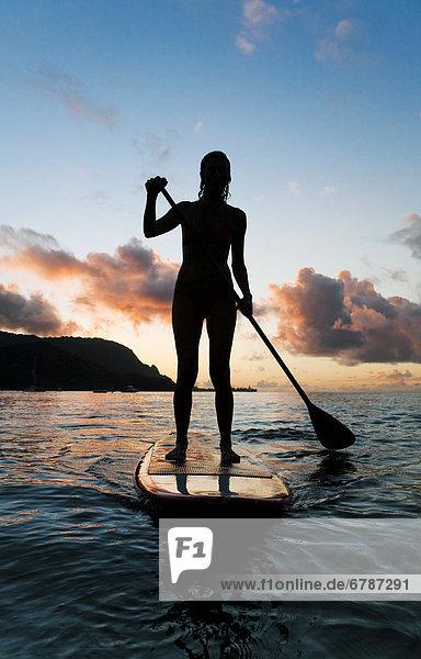 Hawaii  Kauai  Frau Stand up Paddeln im Ozean  schöne Sonnenuntergang.
