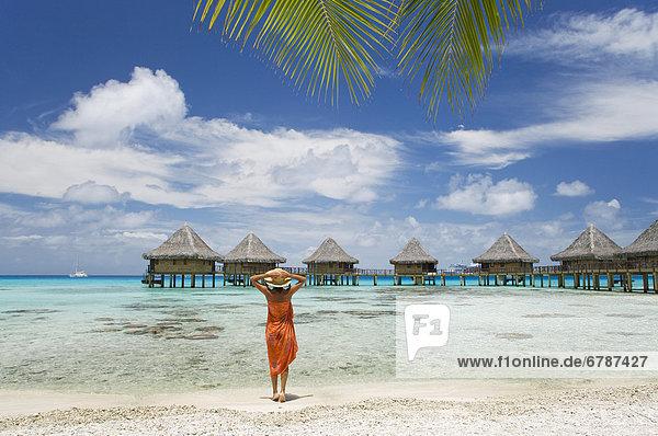 Französisch-Polynesien  Tuamotu-Inseln Rangiroa Atoll  Frau am Strand in der Nähe von Luxus-Resort.