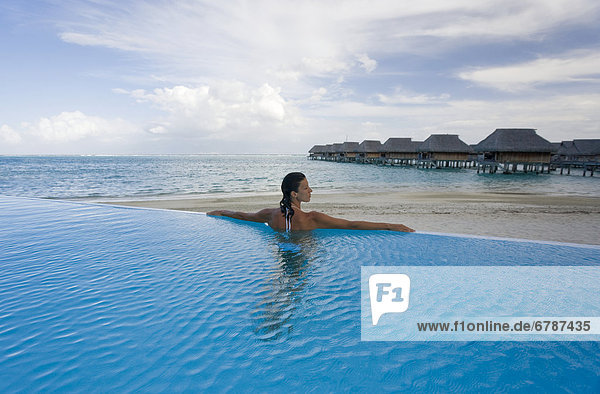 French Polynesia  Moorea  Woman relaxing in resort pool  Luxury resort bungalows in background.