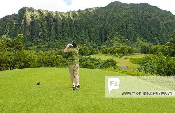 Hawaii  Oahu  Honolulu  Ko'olau Golf Course  Man driving on the 5th hole with beautiful mountain view.