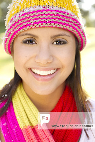 Portrait of woman wearing winter clothing  Snowflakes on cap.