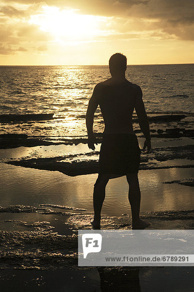 Hawaii  Oahu  Silhouette of fit man standing on the rocky coastline as the sun sets.