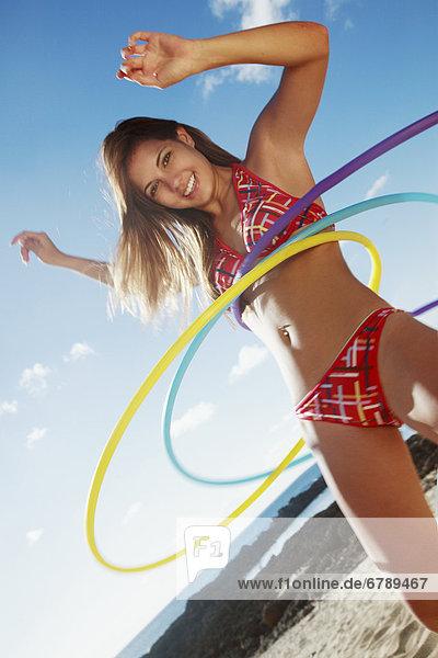Hawaii  Oahu  attraktive junge Frau auf dem Strand Hula hooping.