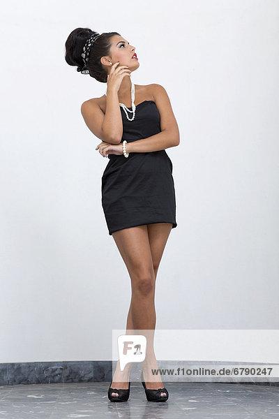 Junge Frau mit Hochsteckfrisur  kurzem schwarzem Kleid und hohen Schuhen