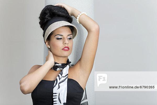 Junge Frau mit Hochsteckfrisur posiert vor Säule  Portrait
