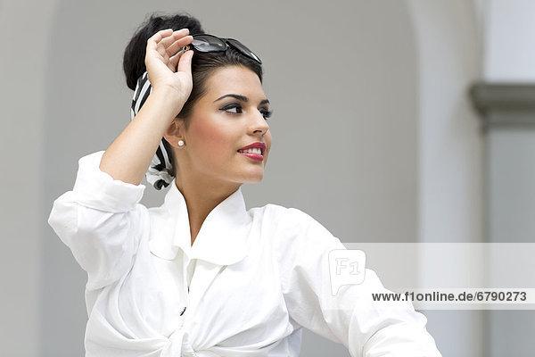 Junge Frau mit Hochsteckfrisur  Sonnenbrille und weißem Hemd