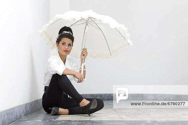 Junge Frau mit Hochsteckfrisur  weißem Hemd  schwarzen Leggins  hohen Schuhen und weißem Schirm posiert sitzend