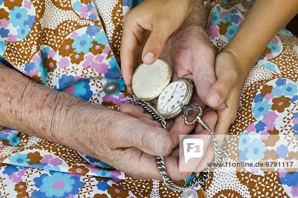 Alte Frau und Kind halten alte Taschenuhr in den Händen