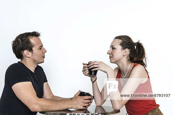 Couple sitting at a table  talking and drinking coffee