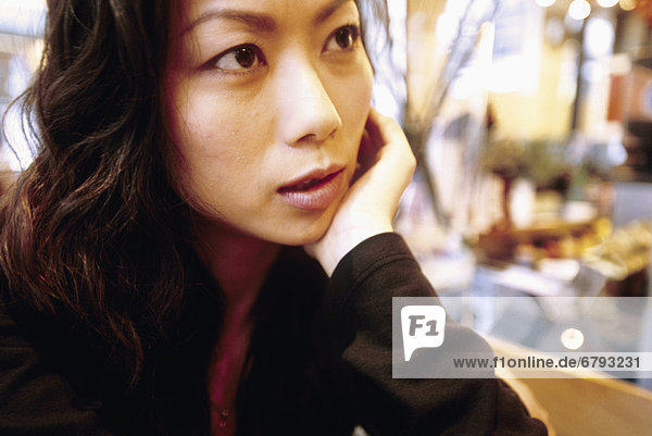 Hong Kong  Woman sitting in local cafe  Close-up of face rested on hand.
