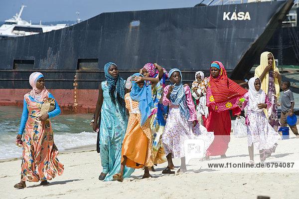 Frauen in traditioneller Kleidung am Strand von Stone Town  Sansibar  Tansania  Afrika
