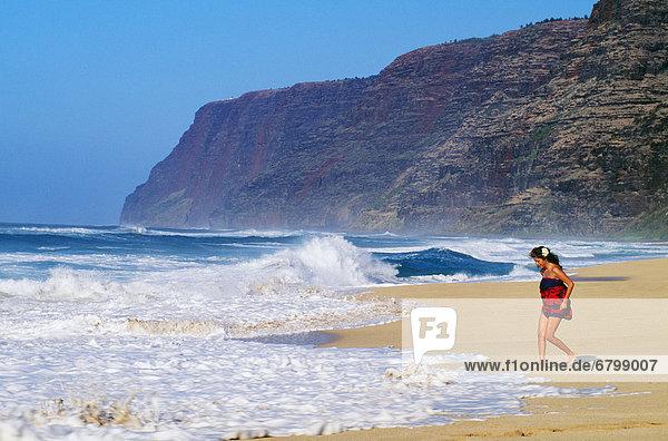 Hawaii  Kauai  Polihale Beach  local woman wearing pareo at shorebreak