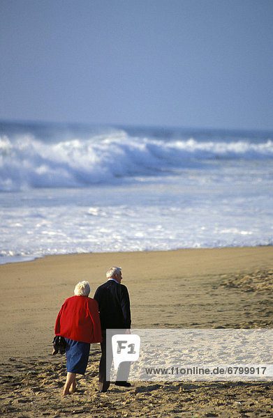 Senior couple walking on beach view from behind  arm in arm  white shorebreak