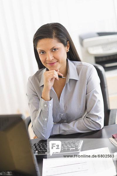 Geschäftsfrau sitzt am Schreibtisch  Portrait