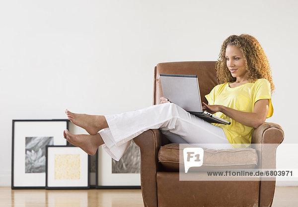 Frau sitzt in Sessel mit laptop