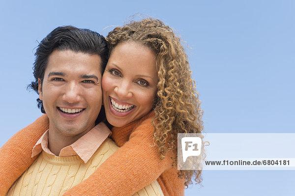 Portrait of couple against blue sky