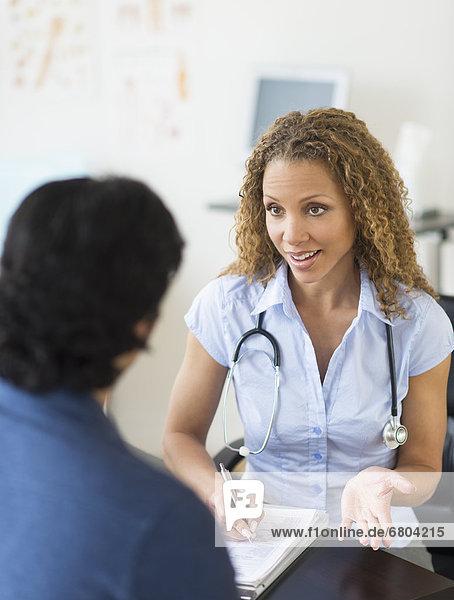 Arzt und Patienten sprechen in Klinik