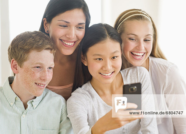 Friends (14-19) looking at mobile phone